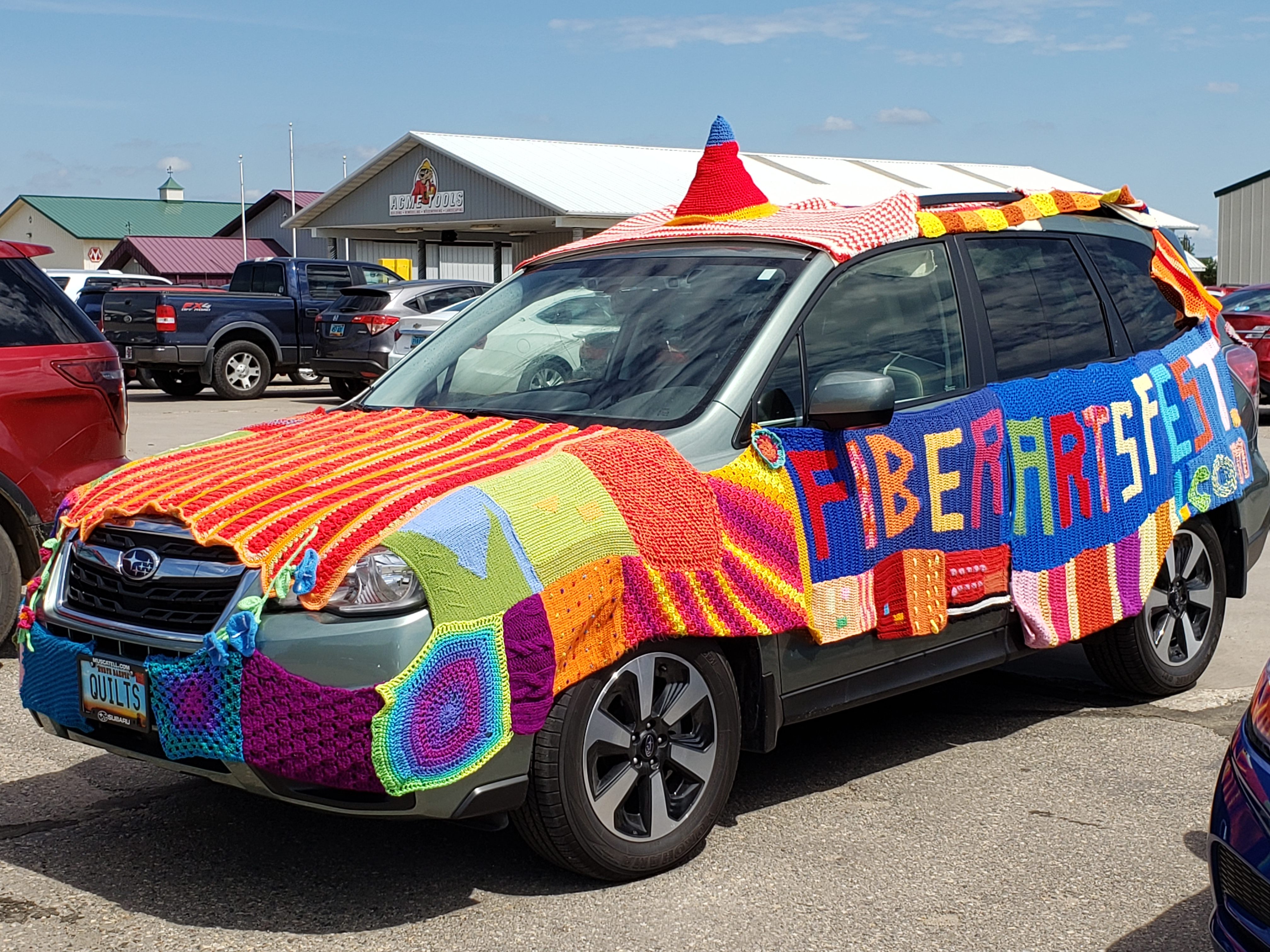 Subaru car 'quilted' with material and the brand 'fiberartsfest.com'